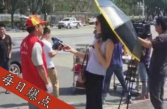 记者打伞访救灾志愿者